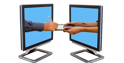 2 computer monitors facing each other with hands sticking out to exchange a signing pad