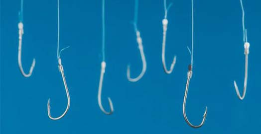 Fishing hooks are hanging with transparent string in front of blue background.