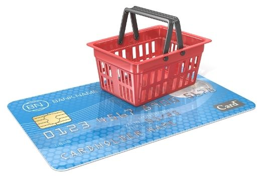 white background with a blue credit card laying face up and a red shopping basket on top of the card