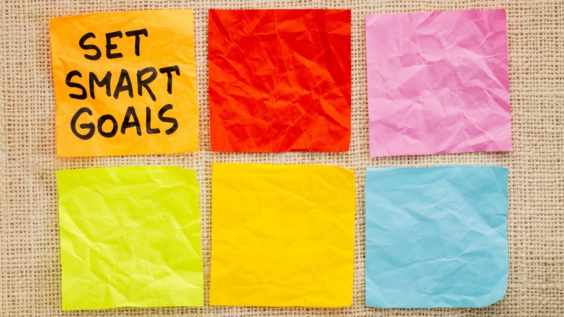 """Cork board with 6 post-it notes. The 1st is orange and says """"Set smart Goals"""". The remaining are blank and colored red, pink, neon green, neon yellow and blue."""