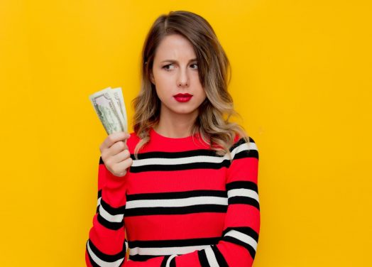 Confused young woman in a red striped sweater with cash on a yellow background.