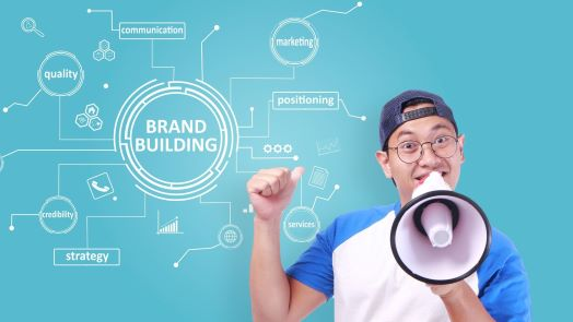 Enthusiastic young man in a blue jersey and a backwards blue baseball cap holdign a megaphoine to his mouth and pointing back to a typography lettering concept of brand building, business marketing motivational quotes and words.